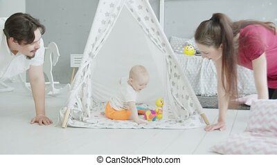 Cute infant playing in hut while parents crawling