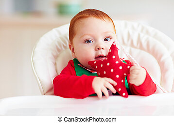 cute infant redhead baby boy in elf costume sitting in...