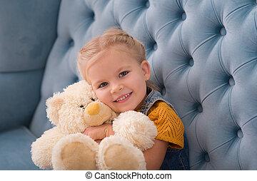 Cute innocent child hugging a teddy bear