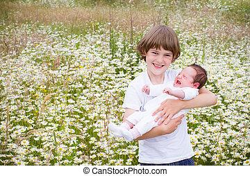 cute, irmã, seu, menino, campo, segurando, margarida, bebê