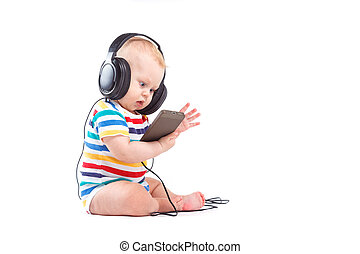 cute joyful baby boy in colorful shirt and headphones on head ho
