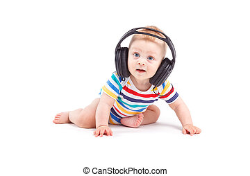 cute joyful baby boy in colorful shirt and headphones on head