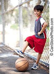 Cute junior boy with basketball under his leg, posing in...