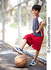 Cute junior boy with basketball under his leg, posing in...