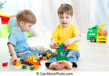 cute kid boy playing with little brother at home