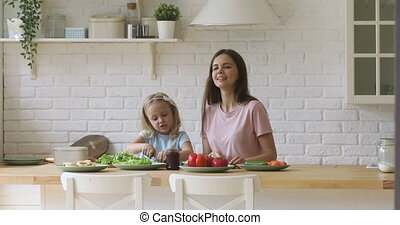 Cute kid daughter helping mom cutting salad together in kitchen