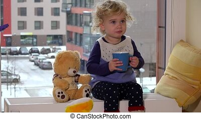 Cute kid drink tea and share with teddy bear sitting on heater near window