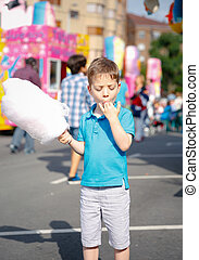 Cute kid eating cotton candy over fair background - Portrait...