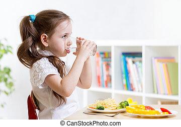 Cute kid girl drinking water in home