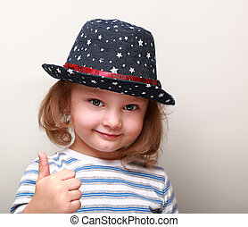 Cute kid girl in blue hat showing thumb up sign