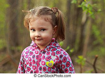 Cute kid girl outdoor in green summer park background
