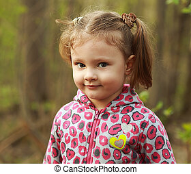 Cute kid girl outdoor on green summer background. Closeup portrait