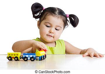 Cute kid girl playing trains