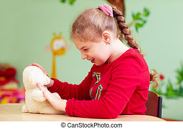 cute kid girl playing with plush toy in kindergarten for children with special need