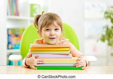 Cute kid girl preschooler with books indoor
