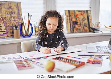 Cute kid girl sitting at home in headphones drawing
