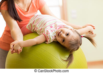 Cute kid girl stretching on pilates fitness ball with mom in gym
