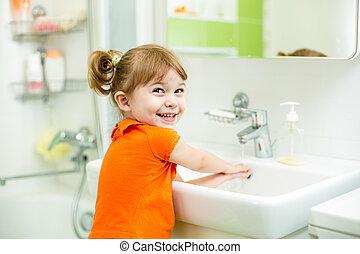Cute kid girl washing in bathroom