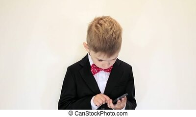Cute kid play businessman, concentrated at work, talking on...