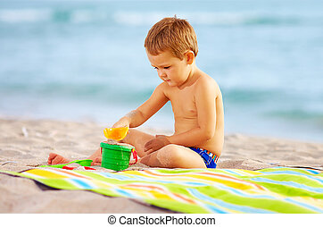 cute kid playing with toys in sand on the beach