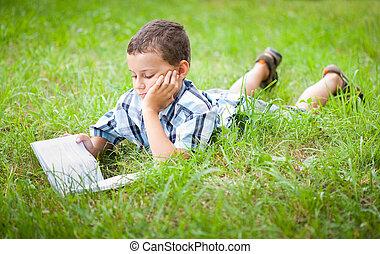 Cute kid reading a book outdoor - Cute kid reading a book...