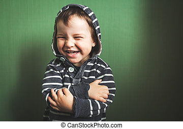 cute kid smiling boy crossing hands in pullover