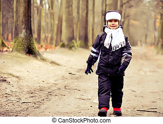 Cute kid taking a walk outdoor in the forest.  Autumn