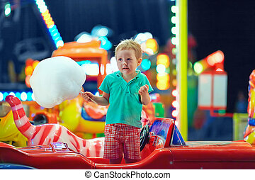 cute kid with cotton candy on carousel