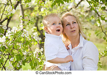 Cute kid with his mom outdoors in nature.