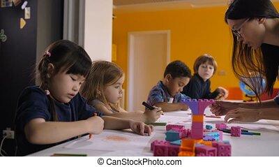 Cute kids drawing with teacher at preschool class - Cute...
