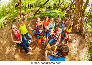 Cute kids having fun with their hands up in forest