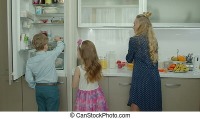 Cute kids helping mother to make breakfast at home