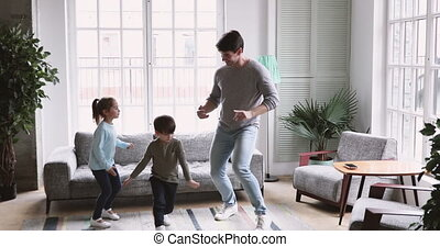 Cute kids imitate father funny moves dancing in living room