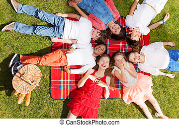 Cute kids laying in a circle on the picnic blanket