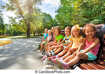 Cute kids on the bench in park toggether