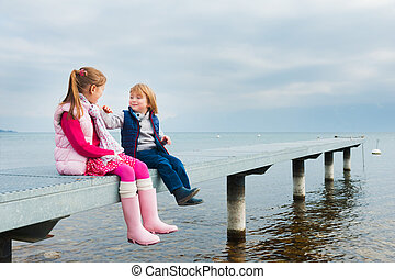 Cute kids playing by the lake, resting on a pier