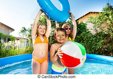 Cute kids playing in big inflatable pool outside