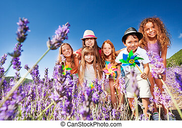 Cute kids playing with pinwheels in lavender field
