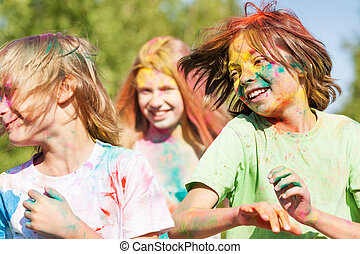 Cute kids smeared with colored powder on Holi fest