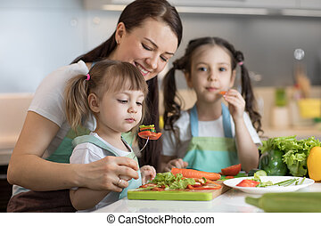 Cute kids tasting vegetables as they prepare a meal with their mother in the kitchen