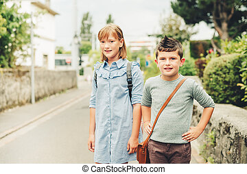 Cute kids with backpacks walking back to school