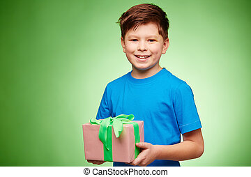 Cute boy with package looking at camera over green background