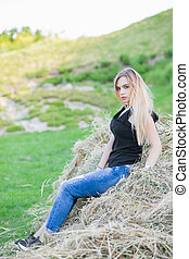 Cute lady posing sitting on the hay.
