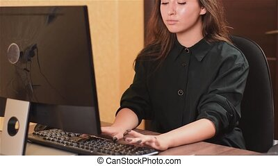 Cute lady working at computer in office. A girl with black nails in a black dress is typing text on a black keyboard and looking at the monitor.