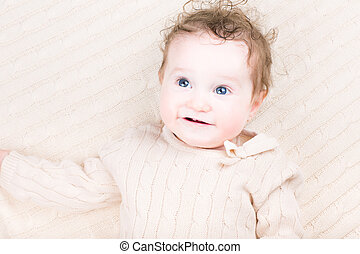 Cute laughing baby girl in a knitted dress