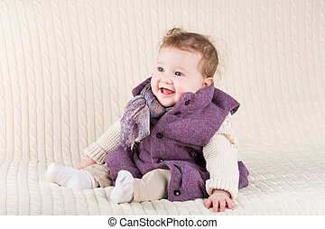 Cute laughing baby girl in a purple jacket sitting on a knitted