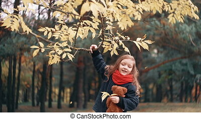 cute, laughing, funny cheerful little girl with teddy bear shakes branch of a tree and yellow autumn leaves fall from it