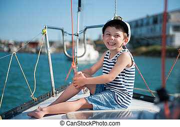 cute laughing happy kid in captain hat sitting on luxury...