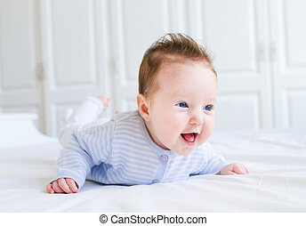 Cute laughing little baby enjoying her tummy time on a white...