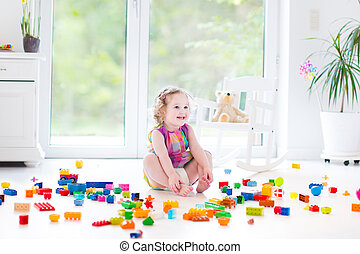 Cute laughing toddler girl playing with colorful blocks